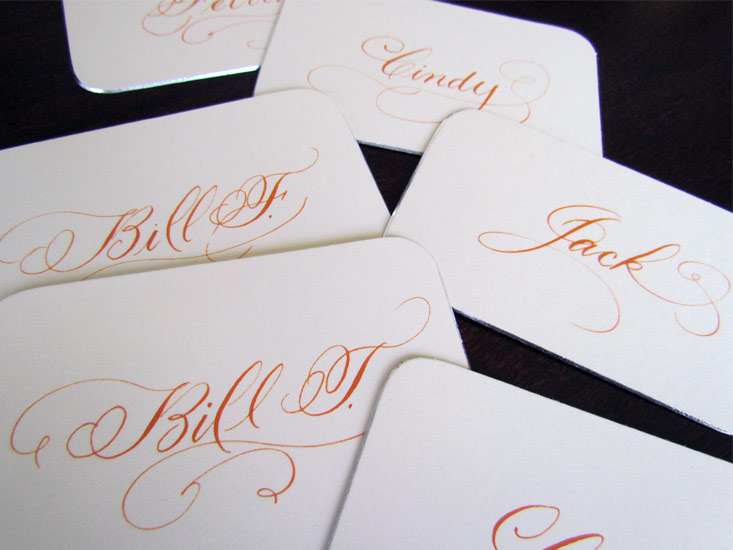 Orange flourished place cards calligraphy by marlean